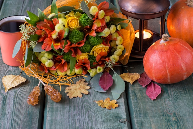 An autumn bouquet of autumn flowers and roses in yellow and orange tones, autumn leaves, a lantern with a candle, a cup of tea and two pumpkins