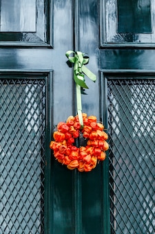 Autumn bouquet of dried orange flowers on a green entrance door to the house. vertical.
