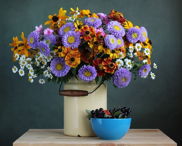 Autumn bouquet of garden flowers in the can and chokeberry. country still life.