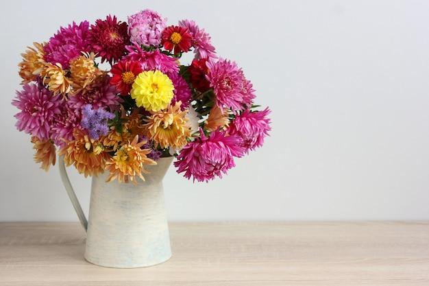 白い背景の上のテーブルの上の水差しにアスターと菊の花の秋の花束