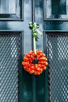 家への緑の入り口のドアに乾燥したオレンジ色の花の秋の花束。垂直。