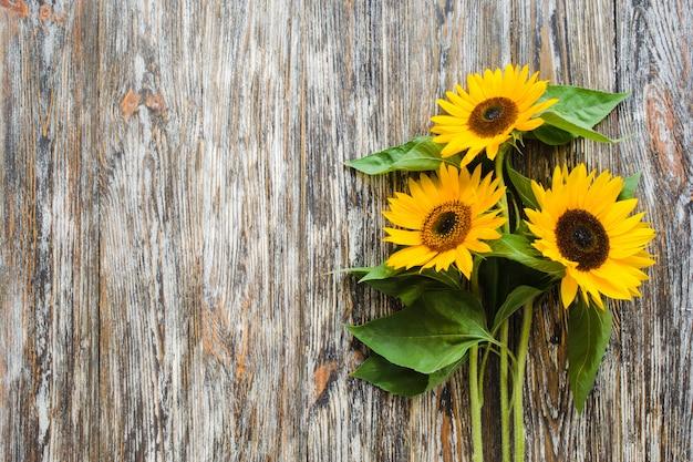 ビンテージテクスチャ木製テーブルに黄色のヒマワリの秋の花束。