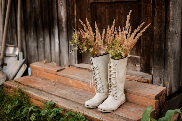 Autumn bouquet rubber boots old wooden village threshold