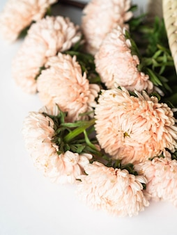 Autumn bouquet of seasonal peach asters in a wicker straw bag on  white background. top view. copy space