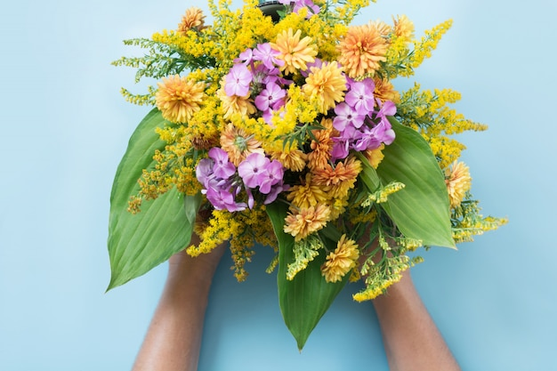 Autumn bouquet of yellow wildflowers in female hand on blue.