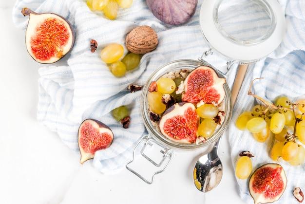 Идеи осеннего завтрака, рецепты. баночка ночного осеннего овса с красным инжиром, виноградом и грецкими орехами. на белом мраморном столе, вид сверху