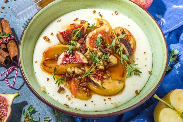 Осенний завтрак или перекус, острая манная каша с карамелизированными яблоками, жареный персик, сливы и инжир, орех, тимьян, мед. вид сверху на синий бетонный стол, освещенный солнцем