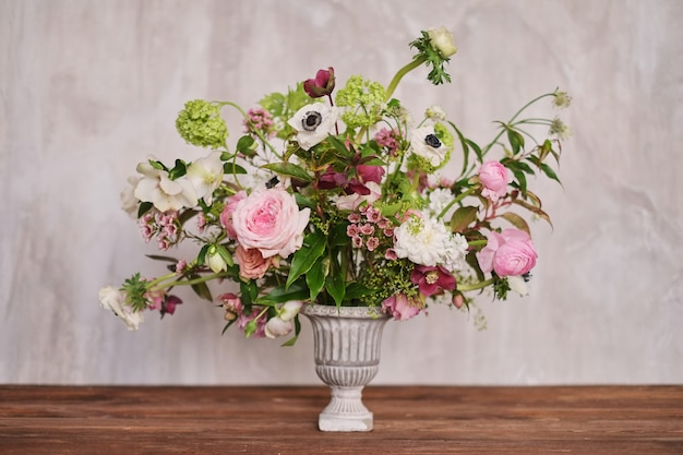 Autumn bridal bouquet of flowers stands on a brown wooden table side view