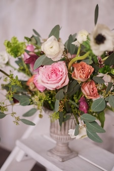 Autumn bridal bouquet of flowers stands on on the white staircase stepladder side view