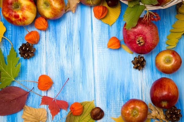 秋の明るい背景。花、葉、青い木製の背景に果物。秋の休日と感謝祭の背景。