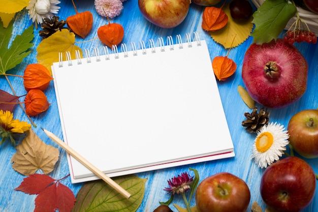 秋の明るい背景。碑文のノート。花、葉、青い木製の背景に果物。秋の休日と感謝祭の背景。