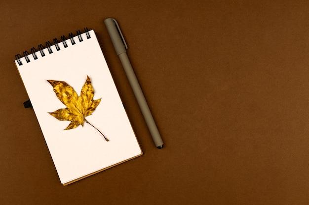 秋のビジネスコンセプト-コピースペースと茶色の背景に金色のカエデの葉とペンで空白のリングバウンドノートブック。