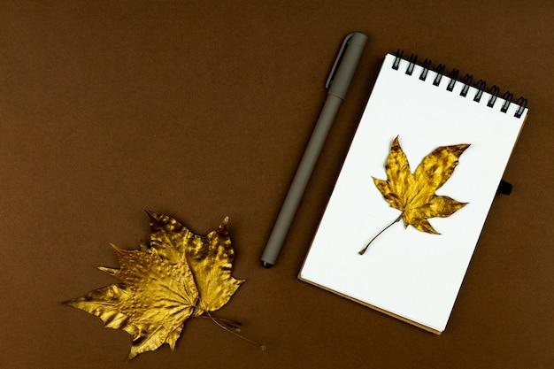 秋のビジネスコンセプト-茶色の平らな場所に金色のカエデの葉とペンが付いた空白のリング製本ノート