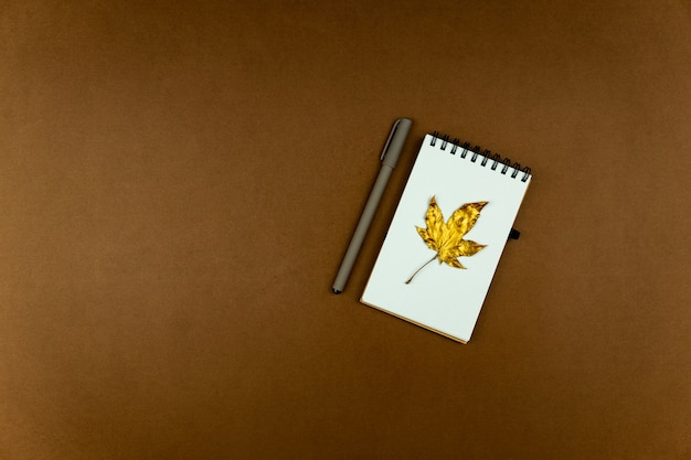 Autumn busines concept - blank ring-bound notebook with golden maple leaf and pen on brown, flat lay