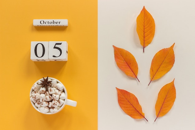 Autumn calendar october 5, cup of cocoa with marshmallows and yellow autumn leaves