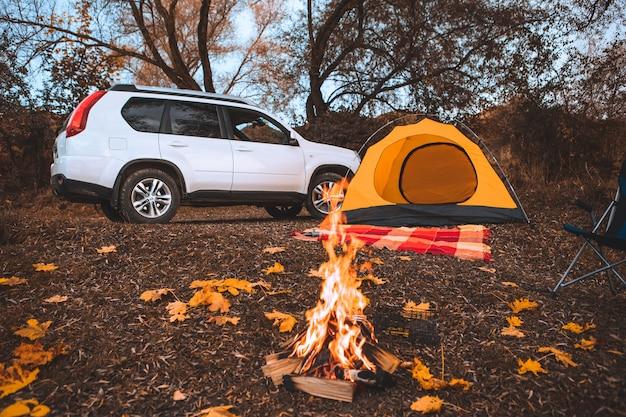 背景のコピースペースに焚き火のテントと車のある秋のキャンプ場