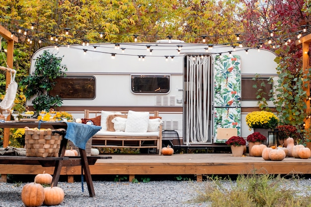 Autumn camping. the trailer is decorated with autumn flower,  pumpkins, decor.