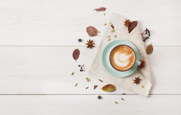 秋のカプチーノの組成物。泡、クローブ、秋の休暇と青いコーヒーカップのトップビュー