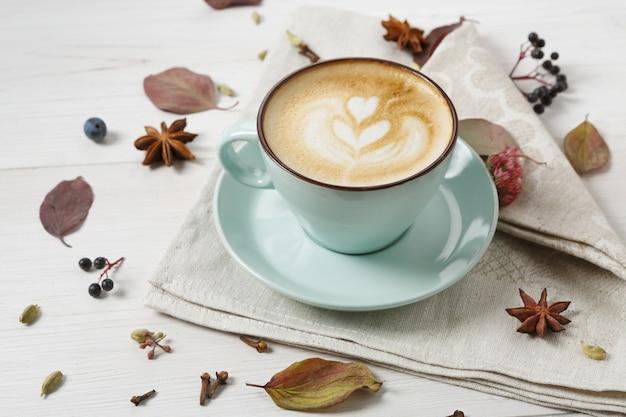 Осенний состав капучино. голубая кофейная чашка с пеной, гвоздикой, осенними цветами