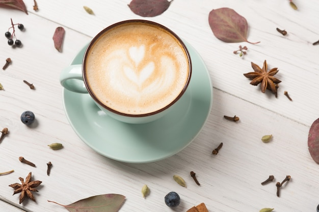 Autumn cappuccino composition. blue coffee cup with foam, cloves, sloe, dried leaves at white wooden table. fall hot drinks, cafe and bar concept
