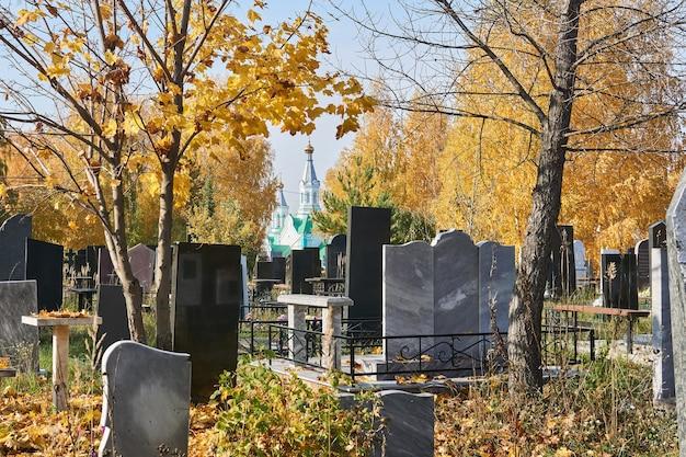 정교회가 내려다보이는 나무가 무성한 가을 묘지