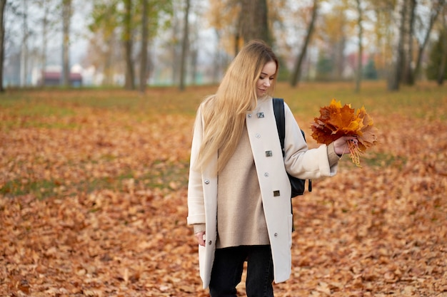 Autumn. cheerful pretty stylish young woman with long blonde hair wearing modern autumn coat