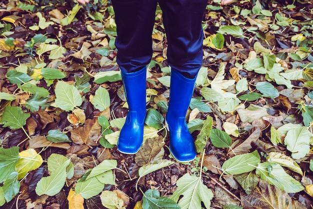 Осенью дети гуляют в лесу с резиновыми сапогами.