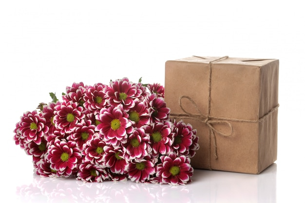 Autumn chrysanthemum flowers and gifts in kraft paper on white isolated