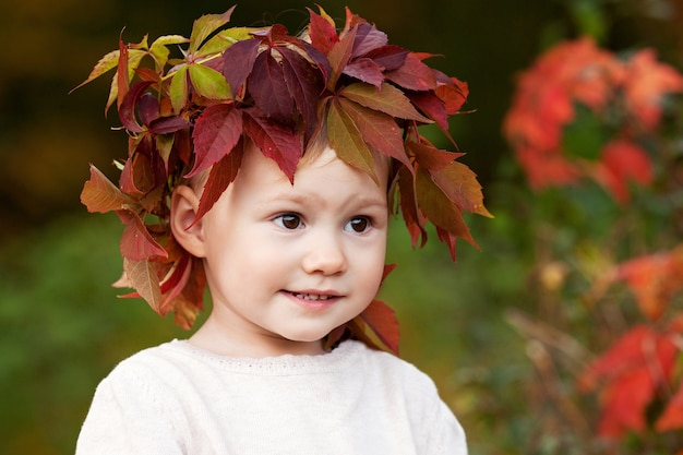 Autumn close up portrait of little  girl. pretty little girl with red grape leaves in autumn park. autumn activities for children. halloween and thanksgiving time fun for family.