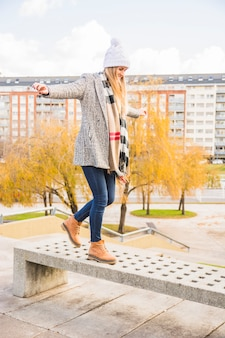 Autumn clothed woman balancing stone bench