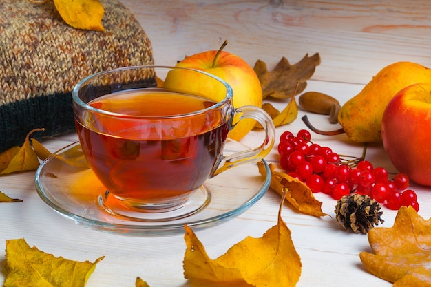 Autumn clothes and a cup of tea on a wooden background