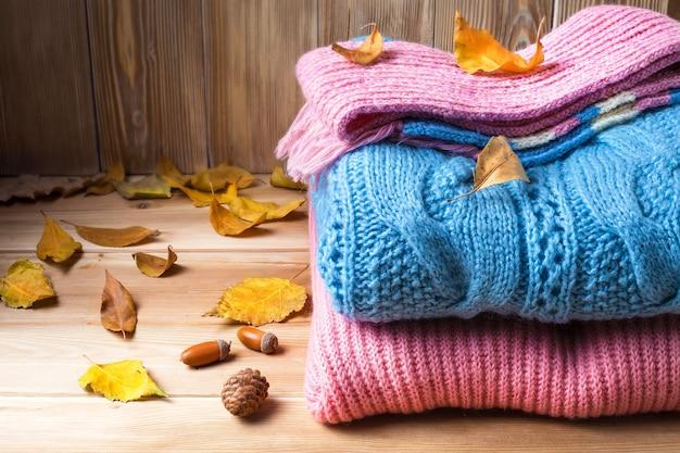 木製の背景に秋の服、セーター、ニットウェア、ウール。テーブルの上の葉、でこぼこ、どんぐり。