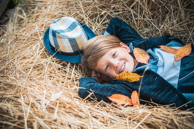 Autumn clothing and color kids trends boy on a breeze in an autumn village autumn child boy with autumnal mood advertisement concept