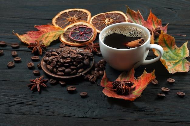 白いカップの秋のコーヒーコーヒーは、木製のテーブルに柑橘系の果物とスパイスを乾燥させ、カラフルなカエデの葉とコーヒーの秋の気分を乾燥させます