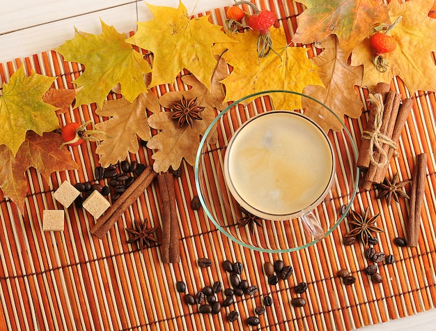 Autumn coffee  with yellow leaves of oak, maple, and coffee in transparent glass mug, cinnamon and sugar