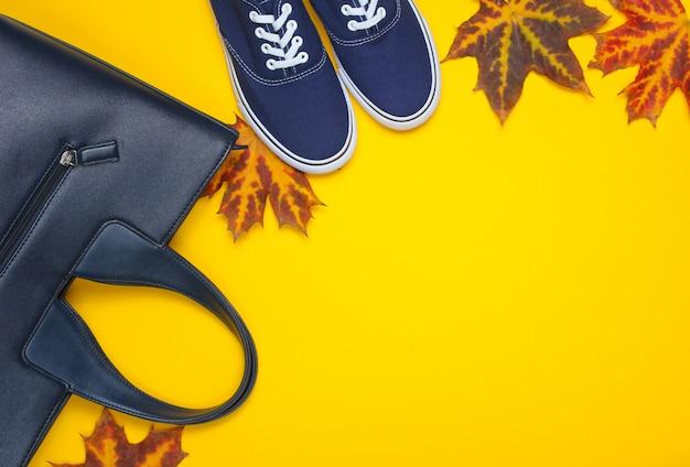 秋のコレクション。革のバッグ、布の靴、黄色に落ちた紅葉。季節のアクセサリー。上面図。コピースペース
