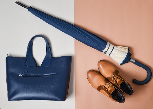 女性のアクセサリーと靴の秋コレクション。デミシーズンブーツ、傘、クリーミーな茶色の紙の背景にレザーバッグ。上面図。