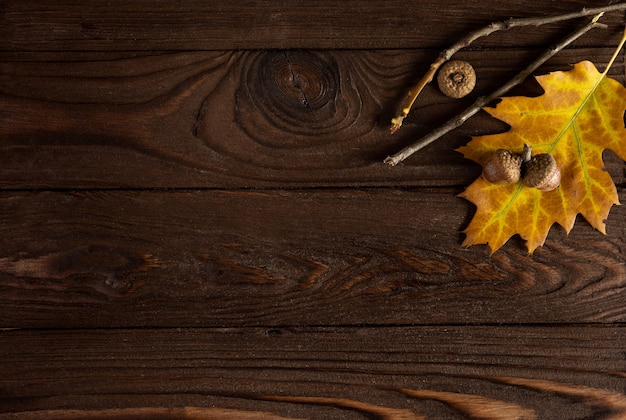 Осень. цветные опавшие листья, желуди на деревянном коричневом фоне, обрамление, макет, копия пространства