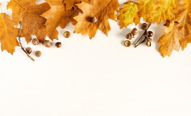 秋。落ち葉、木製の白い背景の上のドングリ