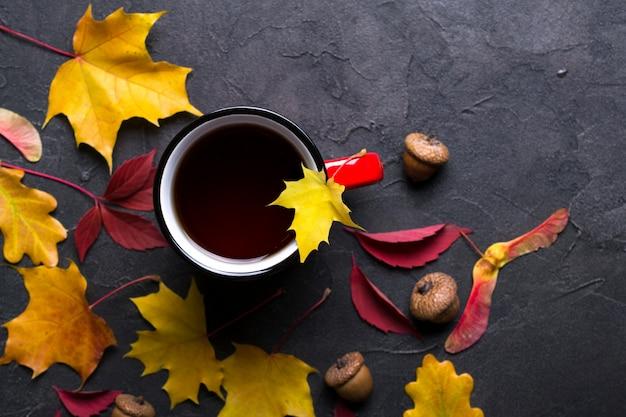 Осенние разноцветные листья и красная чашка чая на темной бетонной поверхности