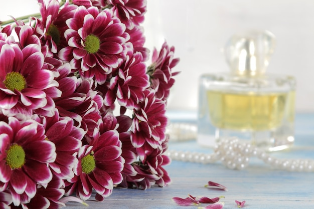 Autumn colors of chrysanthemum and perfume on a blue wooden table