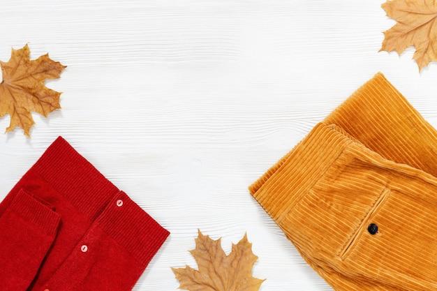 秋の快適な服。トレンディなコーデュロイオレンジパンツと白い木製の背景に暖かい赤いジャケット。女性の服。ファッションのコンセプトです。フラット横たわっていた。上面図。