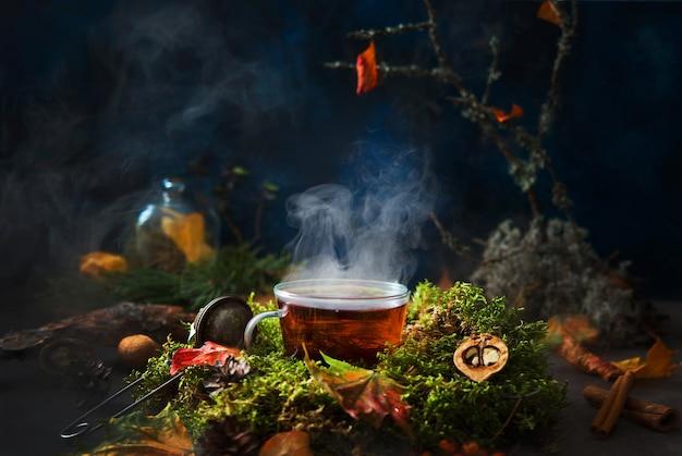 秋の構図、森の風景に囲まれた湯気のある熱いお茶、クリエイティブな写真