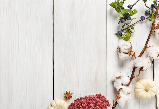 秋のコンポジションの背景。乾燥した秋の花、枝と紅葉、綿とスローで作られたボーダー。上面図
