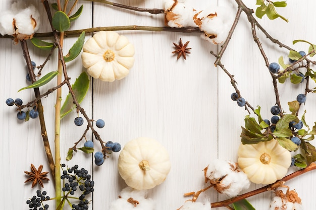 秋のコンポジションの背景。乾燥した秋の花、カボチャ、枝、紅葉、また綿、クローブ、スローで作られたフレーム。上面図