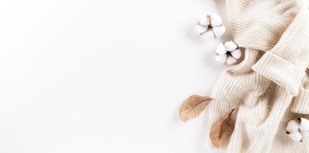 秋の構成。綿の花、紅葉、白い背景の上の女性のセーター。フラットレイ、コピースペース付きの上面図。
