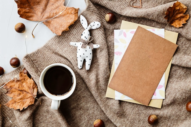 Autumn composition. cup of coffee, blanket, autumn leaves, paper on brown