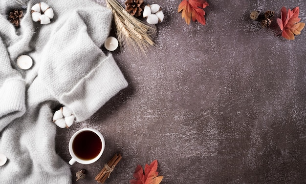 Autumn composition. a cup of coffee, cotton flowers, autumn leaves and sweater on dark stone background. flat lay, top view with copy space.