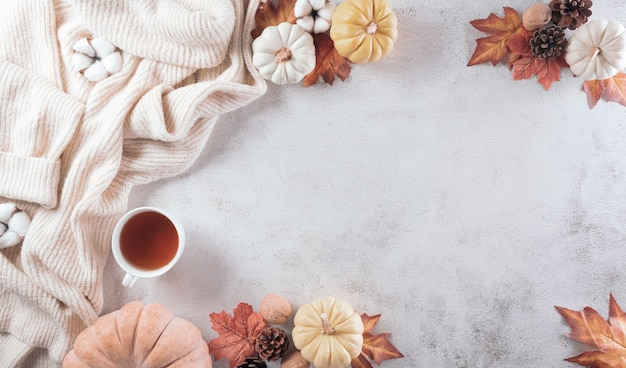 Autumn composition a cup of coffee cotton flowers autumn leaves and sweater on stone background