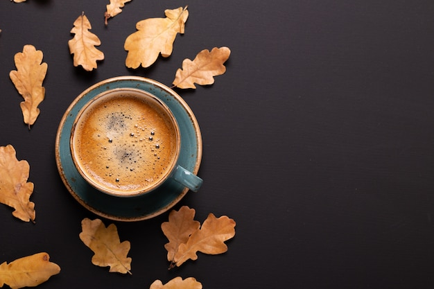 Autumn composition. cup of coffee and dry leaves on black background.
